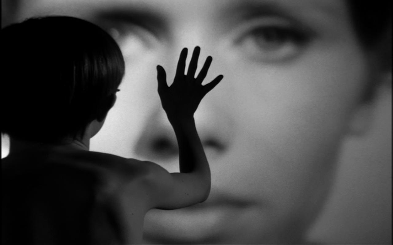 En pojke håller sin hand över en stor bild av Liv Ullmans ansikte.