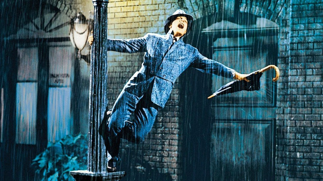 "Gene Kelly snurrar runt en lyktstolpe en regnig afton i ""Singin' in the Rain"""
