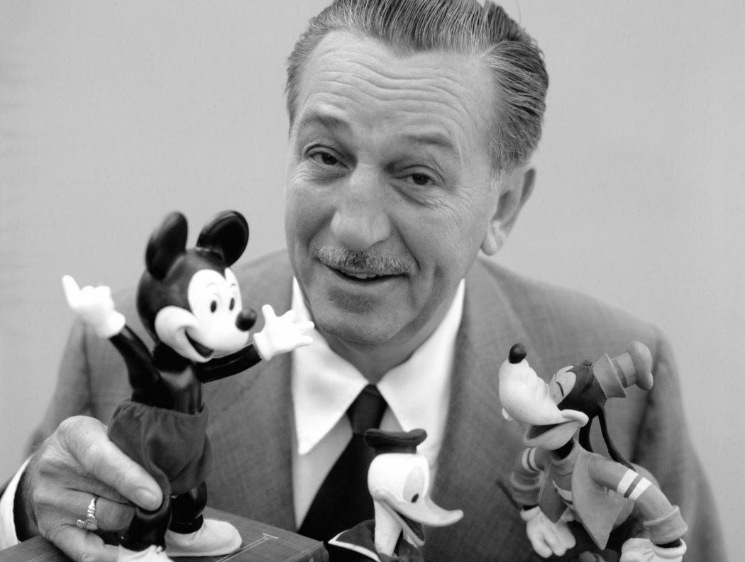 Walt Disney sitter med leksaksfigurer av Musse Pigg, Kalle Anka och Långben.