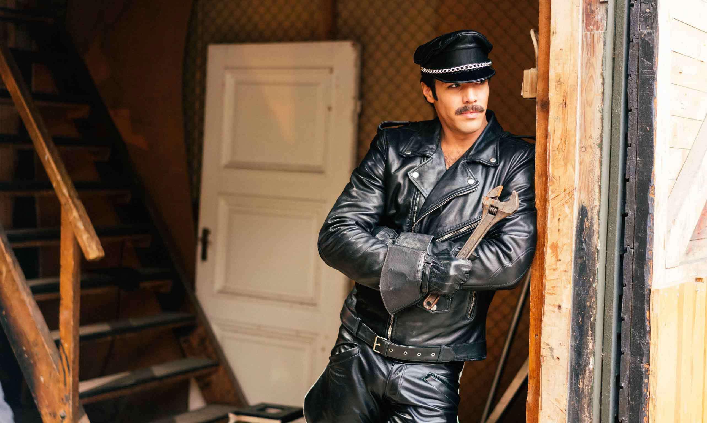 Från Tom of Finland, Finlands bidrag till Oscarsgalan. En man i läderkläder står lutad mot en vägg med en stor skiftnyckel i handen.
