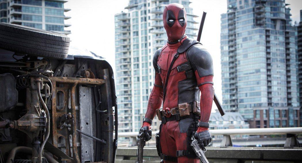 Deadpool står på en bro bredvid en vält bil efter en fight.