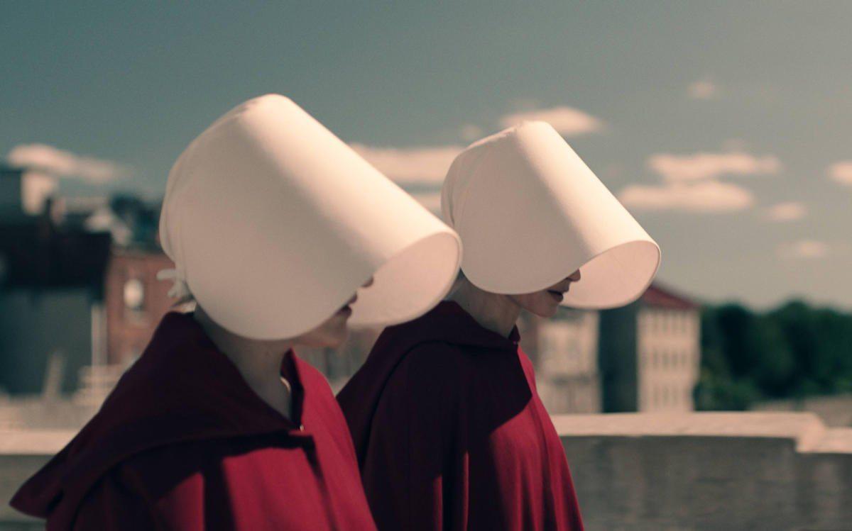 Två kvinnor går bredvid varandra i sci-fi serien The Handmaid's Tale.