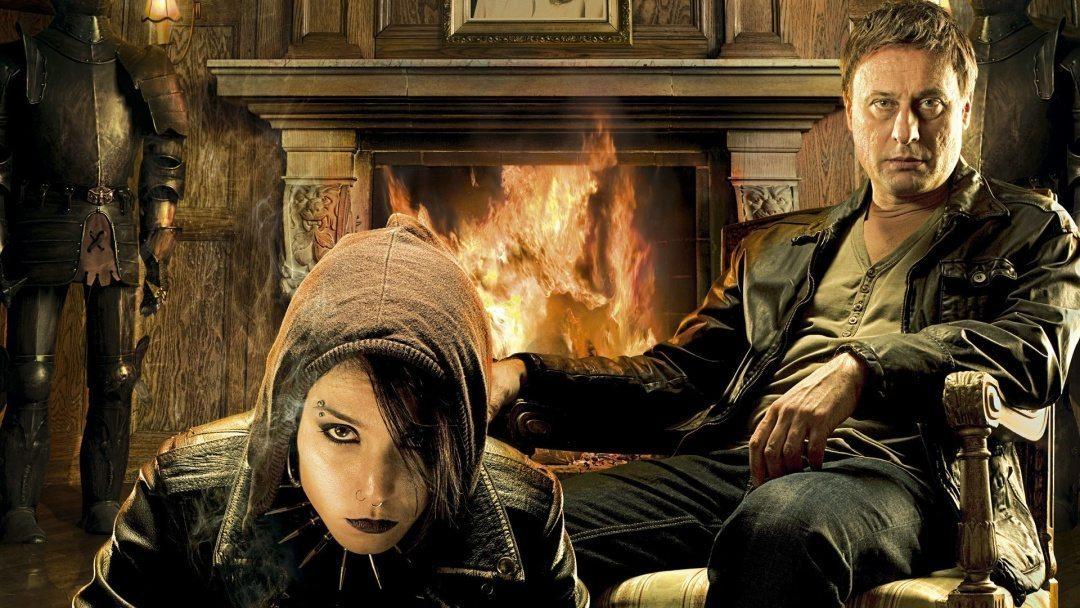 Noomi Rapace och Michael Nyqvist i Män som hatar kvinnor. De sitter framför en öppen spis och tittar in i kameran.