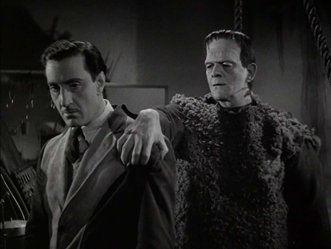 Ur Frankensteins son. Monstret till höger står bakom Frankenstein och håller en hand på hans axel.