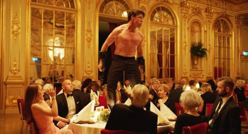 """Ur """"The Square"""" av Ruben Östlund. En man i bar överkropp står på ett matbord i en stor salong."""