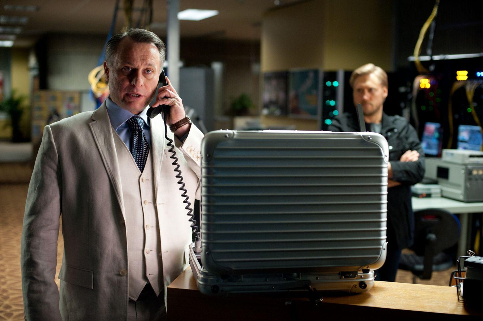 Michael Nyqvist i Mission: Impossible - Ghost Protocol. Han talar i telefon med en öppen portfölj framför sig.