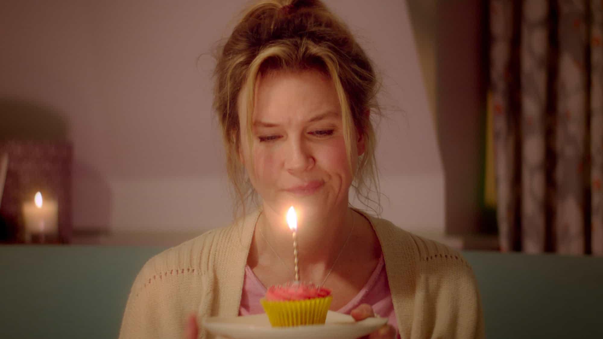 Bridget Jones sitter och firar sin födelsedag själv med en cupcake med ett ljus i.