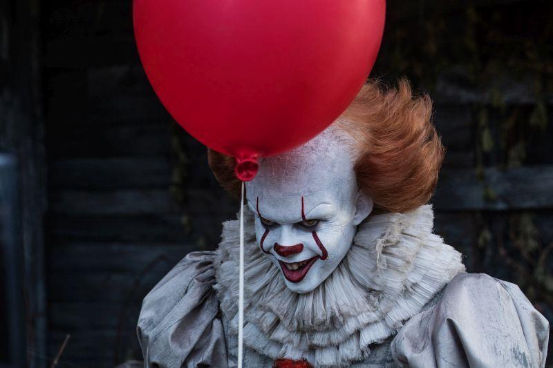 Bill Skarsgård som clownen Pennywise i skräckthrillern Det. En röd ballong svävar framför honom.