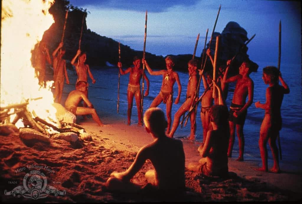 Pojkarna i Flugornas herre dansar runt lägerelden på en strand.