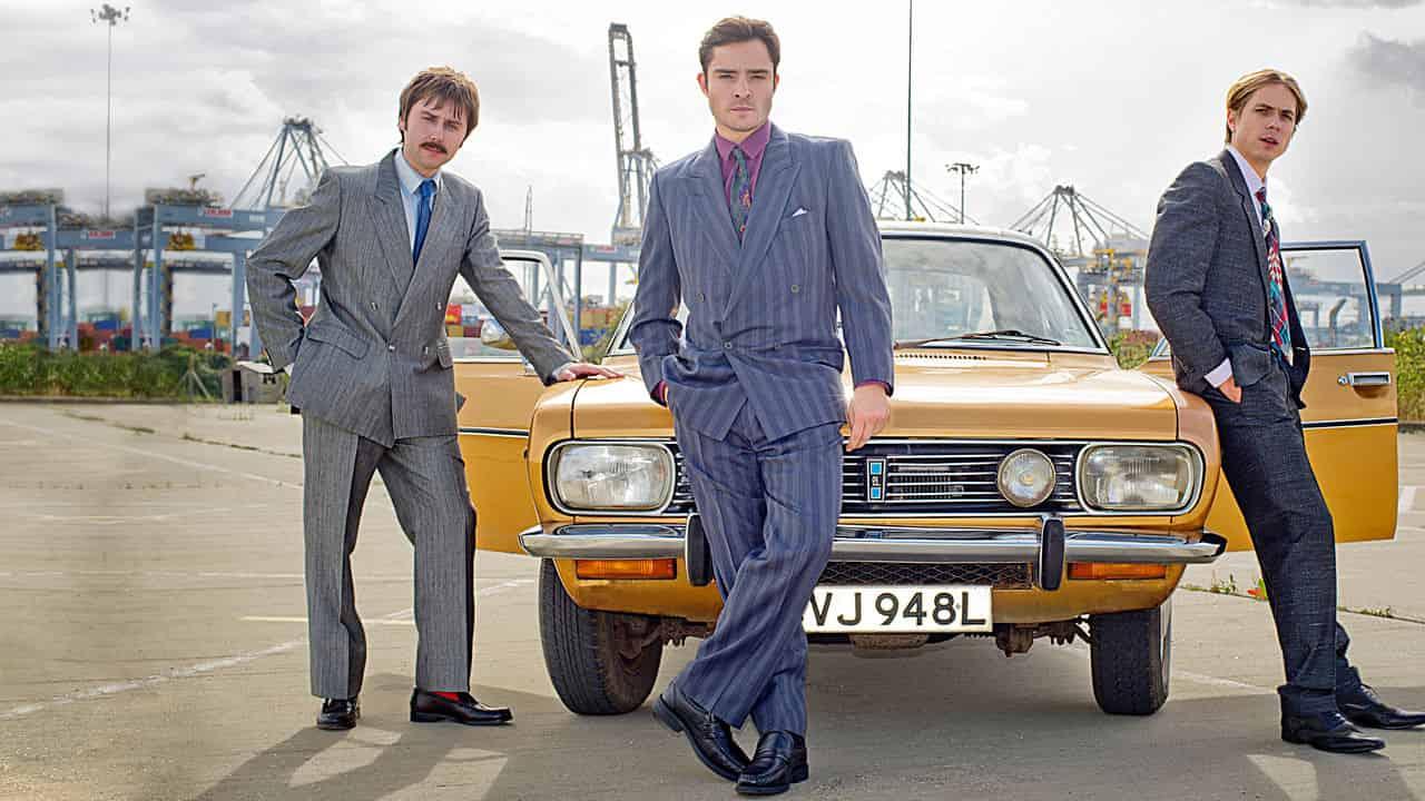 Vincent (Westwick), Brian (Buckley) och Lavender (Thomas) från White Gold står lutade mot en gul bil.