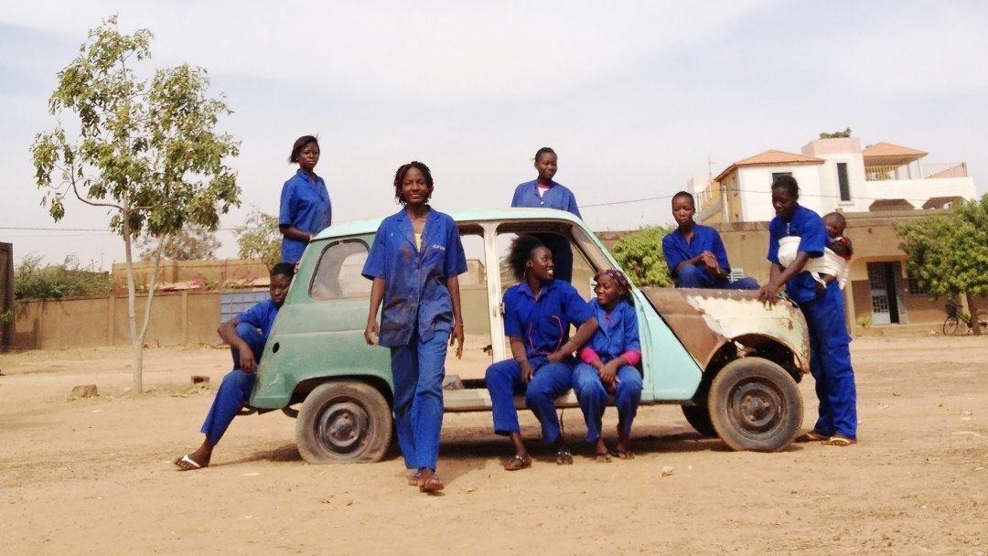 Från Ouaga Girls, en dokumentärfilm av Theresa Traore Dahlberg. Kvinnorna står i blåa arbetskläder utomhus runt en turkos bil.