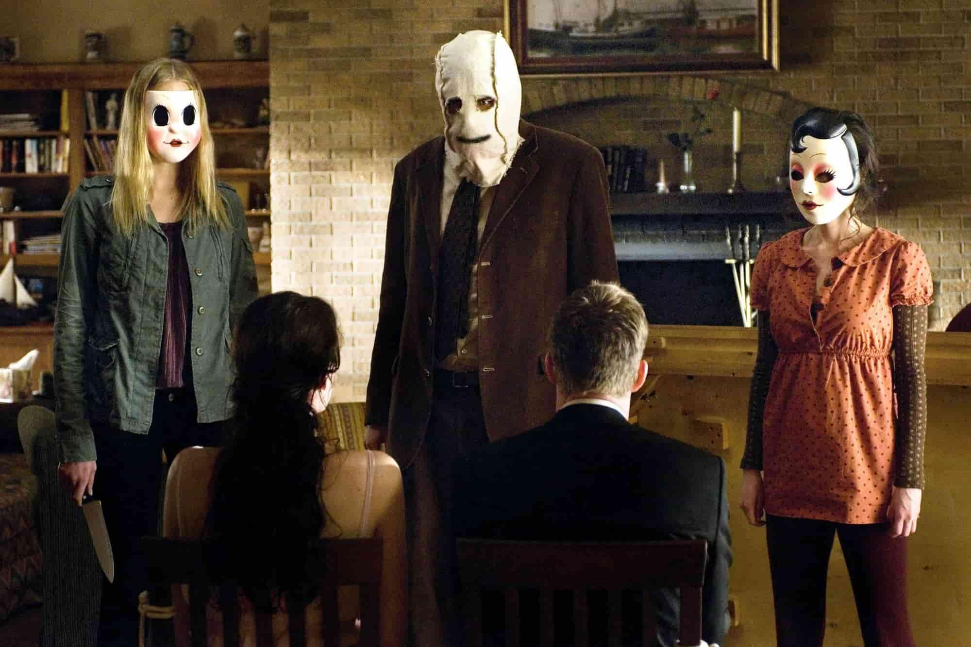 Från The Strangers. Tre maskerade personer står i ett vardagsrum och tittar på två andra personer som sitter fastbundna på varsin stol, framför dem.