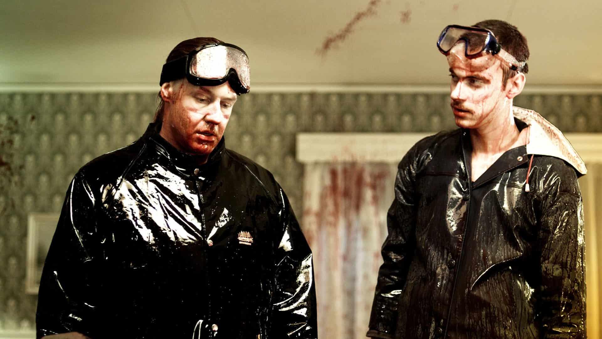 Två män står blodiga i svarta kläder. Från Arme Riddere av Jo Nesbø.