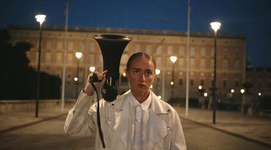 Silvana står framför det kungliga slottet med en megafon i handen.