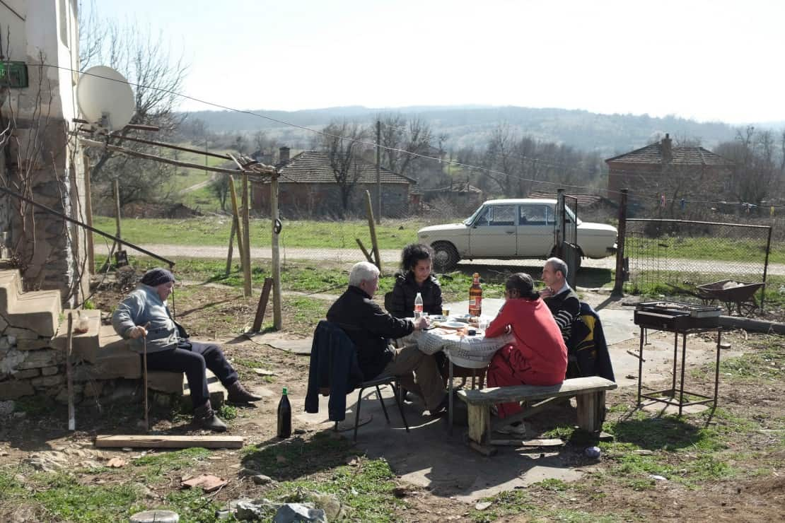 """Från filmen """"The Good Postman"""" i regi av Tonislav Hristov. På bilden syns fyra personer sitta utomhus vid ett bord."""