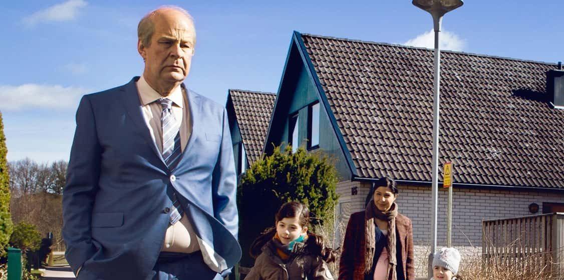 Från En man som heter Ove. En man står på gatan o blå kostym med en kvinna och två barn till höger om sig.