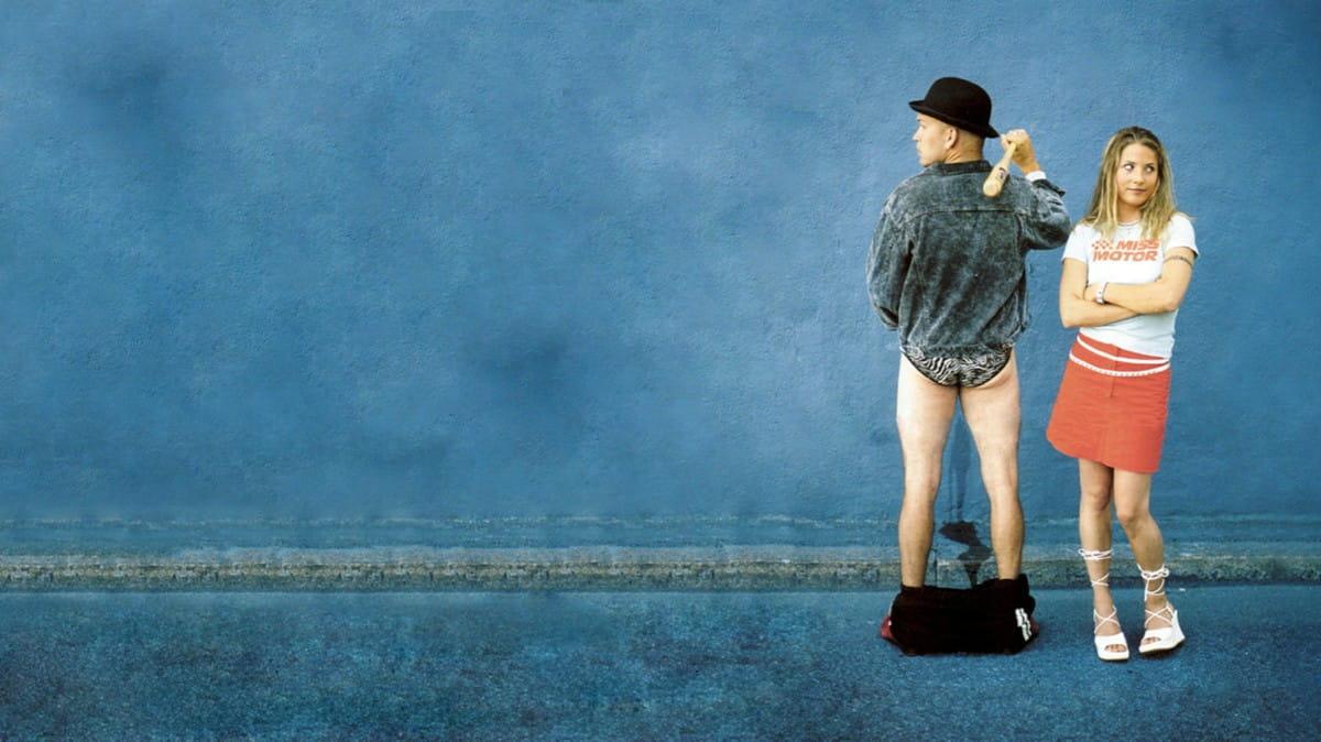 Från Smala Sussie. En man och en kvinna står till höger i bild. Mannen har dragit ner byxorna för att kissa och kvinnan tittar uppgivet bort.