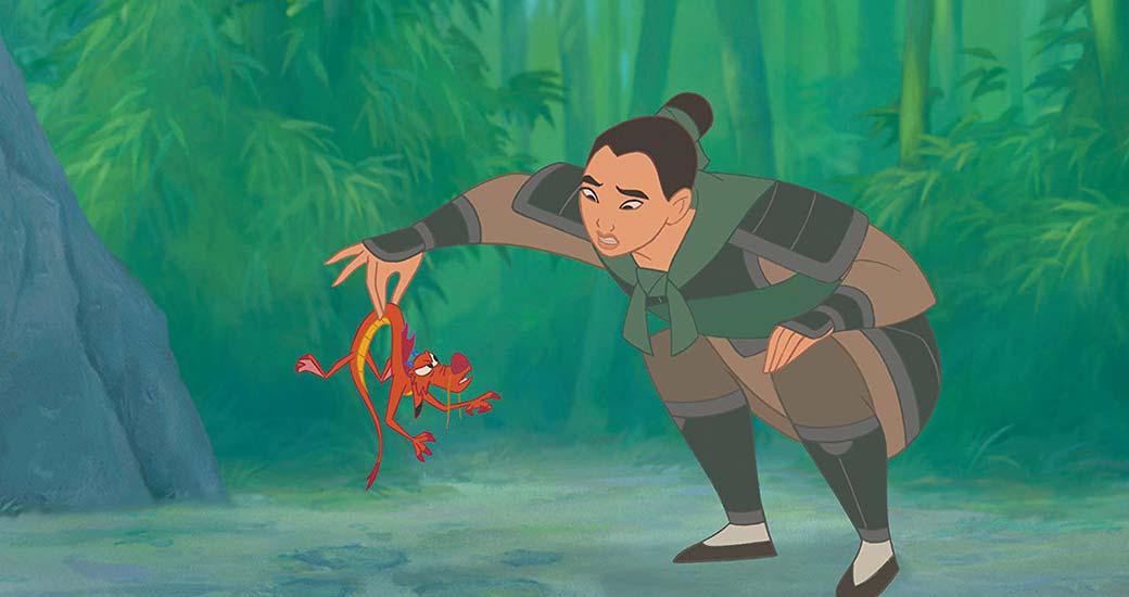 Mulan lyfter upp sin drakkompis Mushu i svansen.