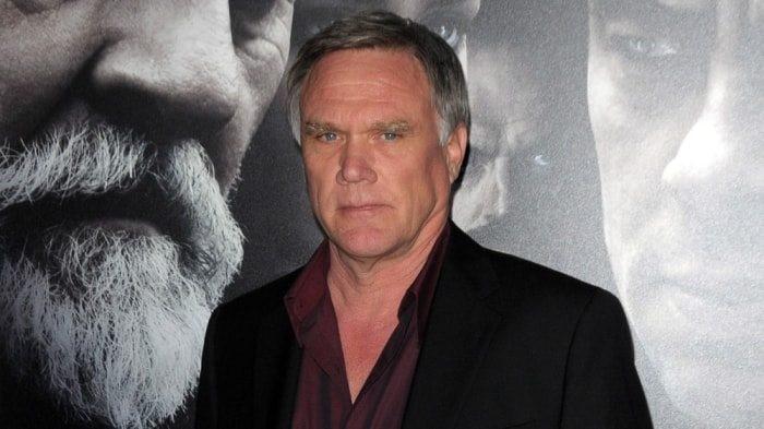 Regissören Joe Johnston som ska regissera den fjärde Narnia-filmen poserar framför en affisch