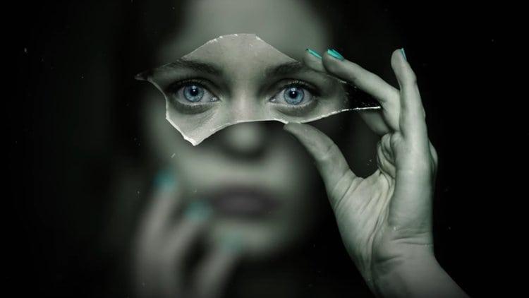 En kvinna håller upp en glasbit framför sitt ansikte och hennes ögon syns tydligt, allt annat är suddigt.