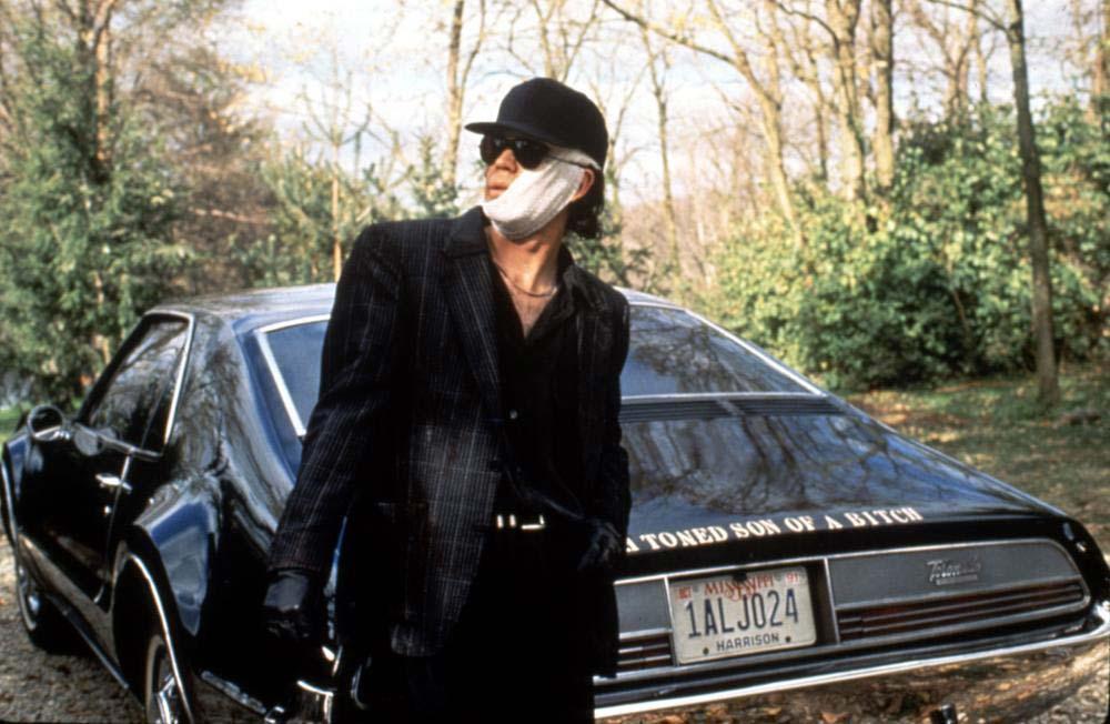 Timothy Hutton står framför en svart bil.