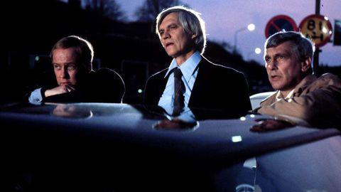 Från kriminalserien Polisen i Strömstad. Tre män tittar upp bakom några bilar.