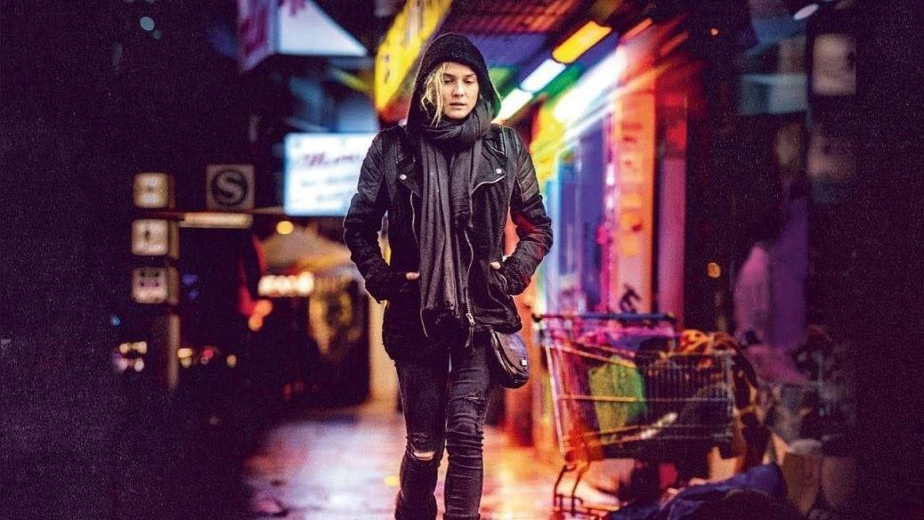Diane Kruger går längs en regnig och neonklädd gata i Utan nåd.