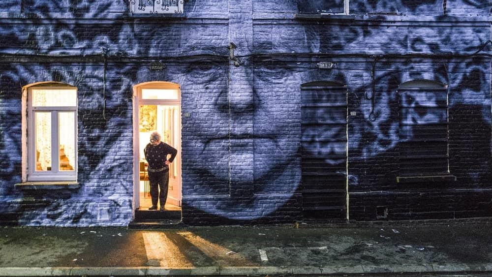 Kvinna i byggnad med sitt eget foto klistrat på fasaden.