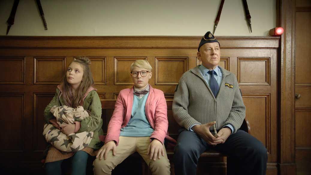Lasse, Maja och en polis sitter på en bänk.