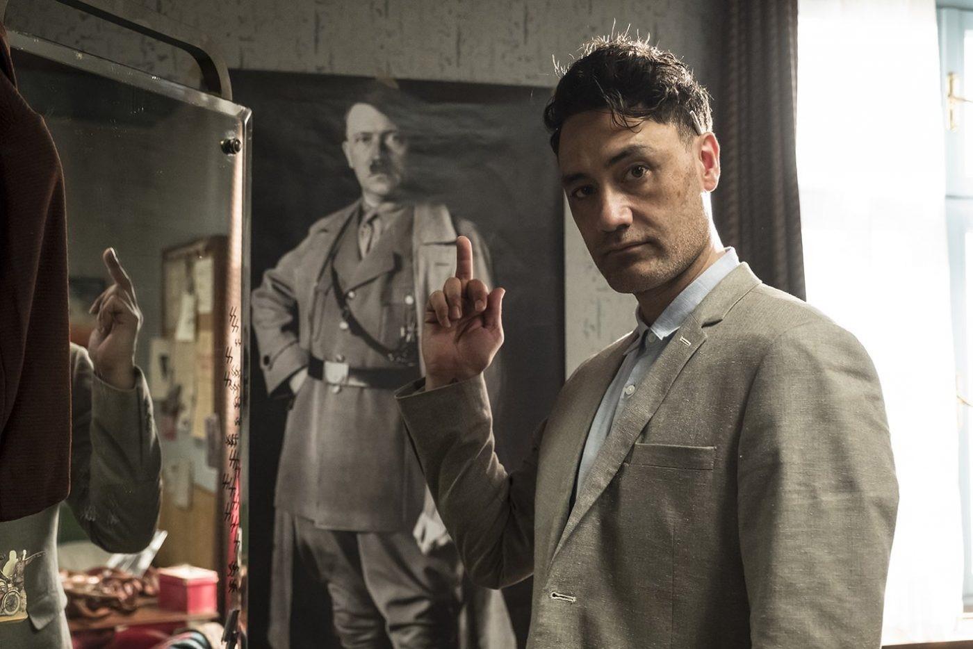 Taika Waititi pekar finger och röker framför en affisch på Adolf Hitler.