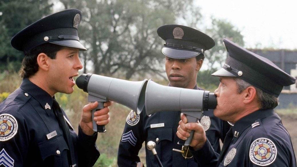 På bilden ser du två poliser ur polisskolan som skriker åt varandra i megafon.