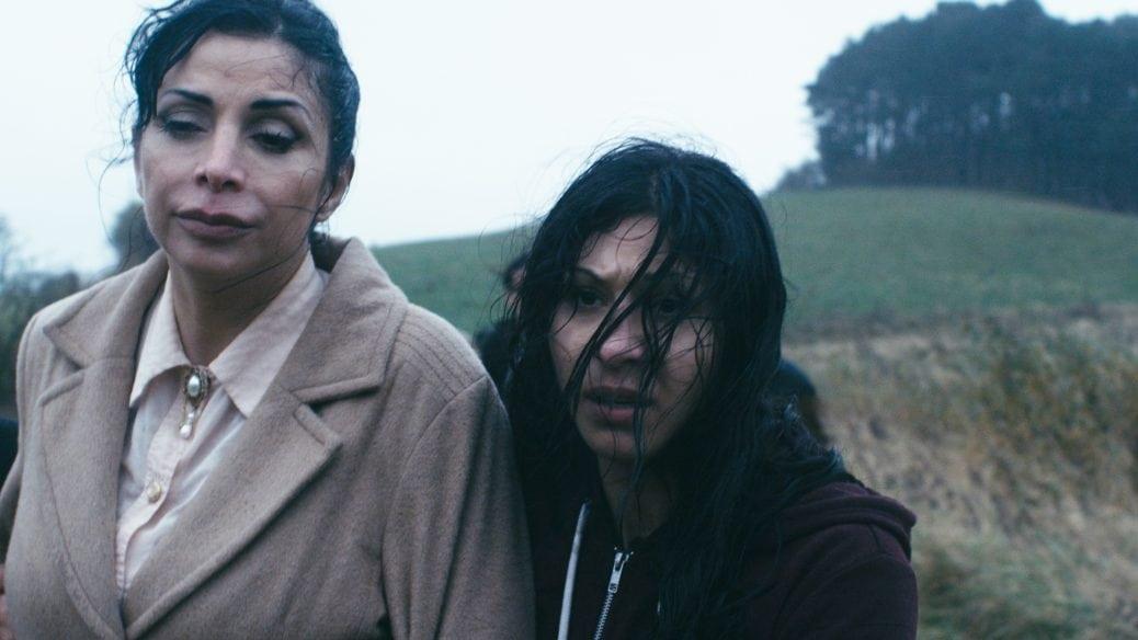 Två kvinnor står på ett fält.