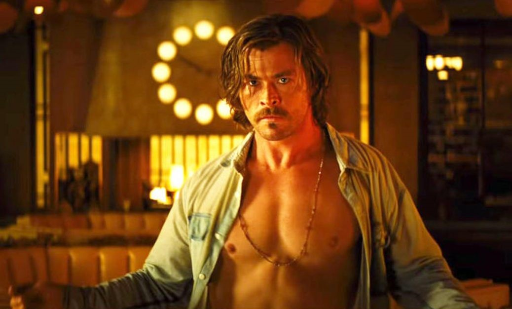 """Chris Hemsworth i """"Bad Times står med uppknäppt skjorta i """"Bad Times at the El Royale""""."""
