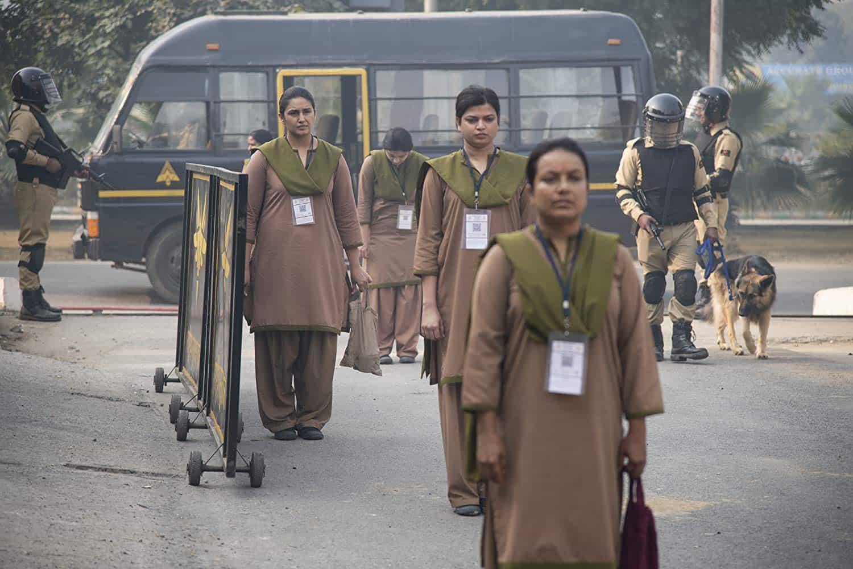 Arbetare, övervakade av beväonade vakter, på väg till jobbet i Leila