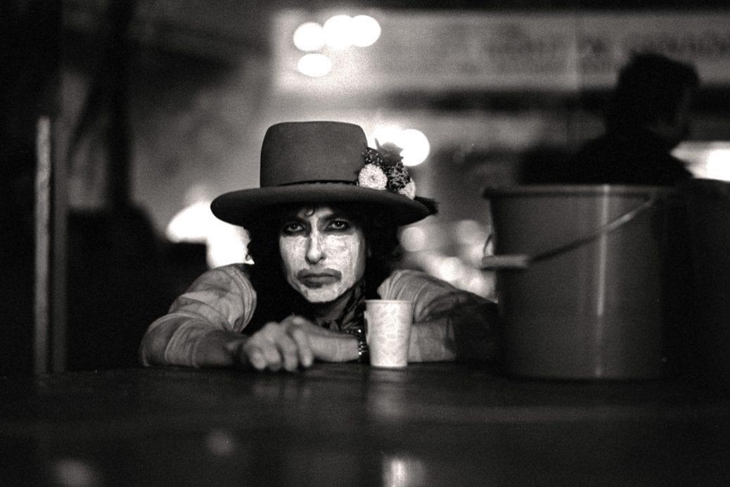 Bob Dylan är vitmålad i ansiktet på en bar, medan han kollar rakt in i kameran.