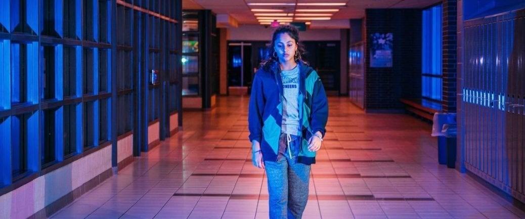 En kvinna går i en skolkorridor i Share.