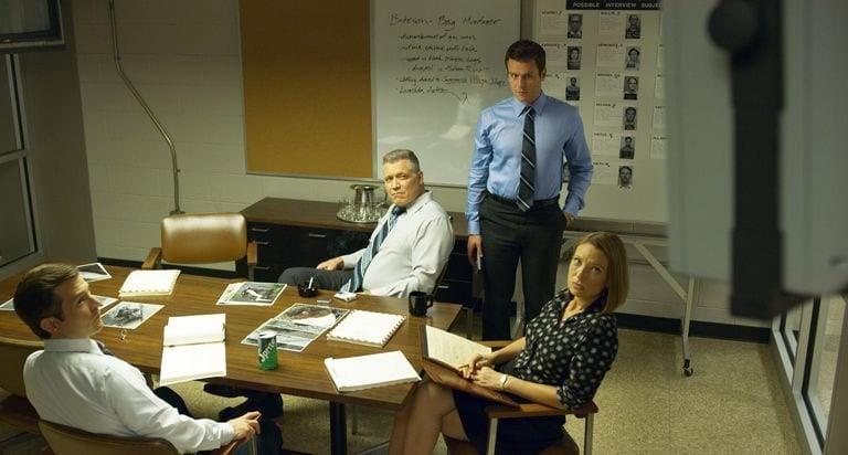 Bild från David Finchers Netflix-serie Mindhunter. Karaktärerna Holden Ford, Bill Tench och Dr. Wendy Carr syns i bild, arbetandes på sitt kontor.