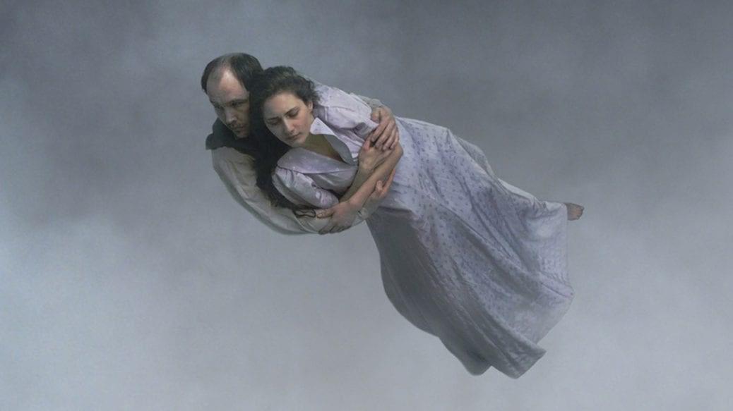 """En man och en kvinna svävar fram genom molnen i Roy Anderssons """"Om det oändliga""""."""