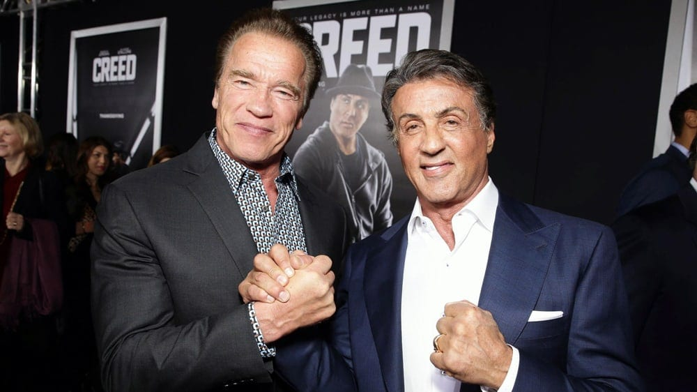 Arnold Schwarzenegger och Sylvester Stallone skakar hand på PR-event