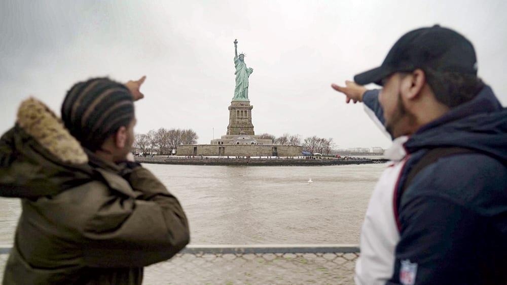En bild ifrån HBO-dokumentären Liberty: Mother of Exiles. Bilden föreställer två unga man pekandes på frihetsgudinnan i bakgrunden.