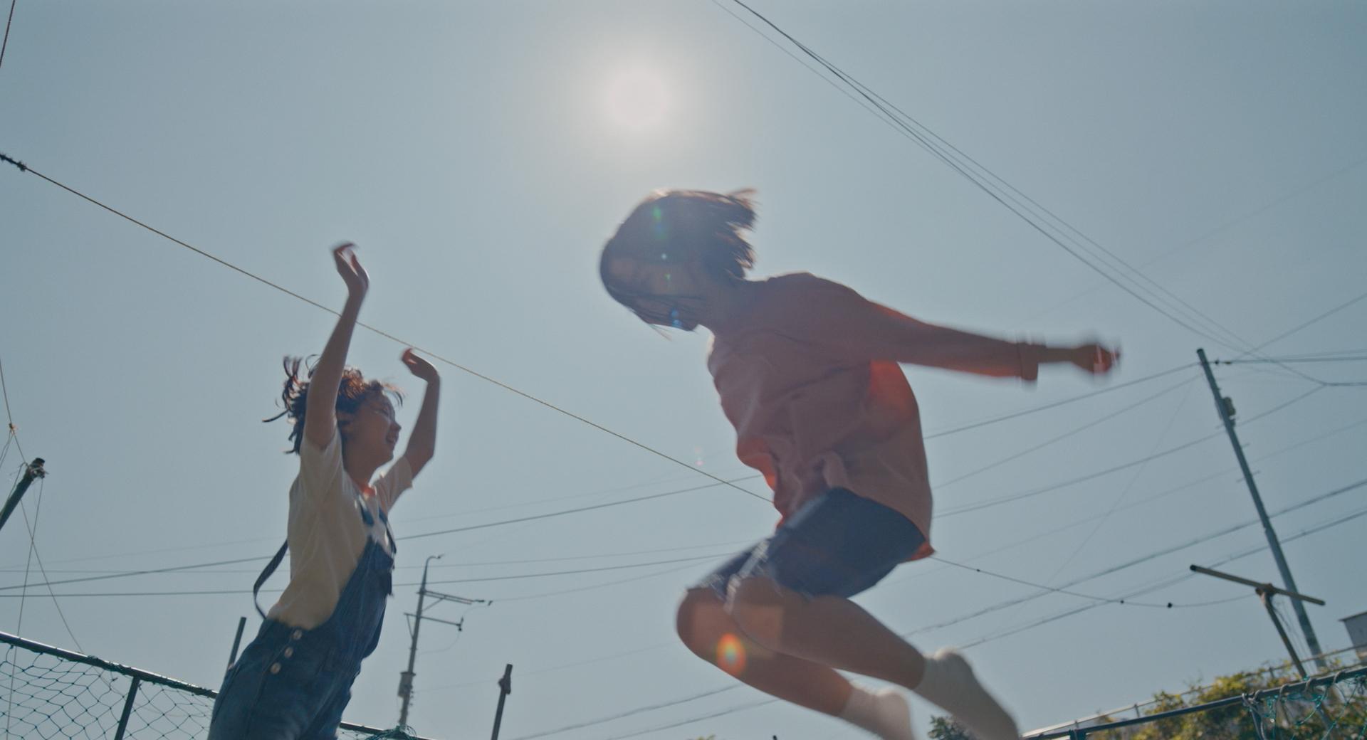 Eunhee hoppar studsmatta med en vän