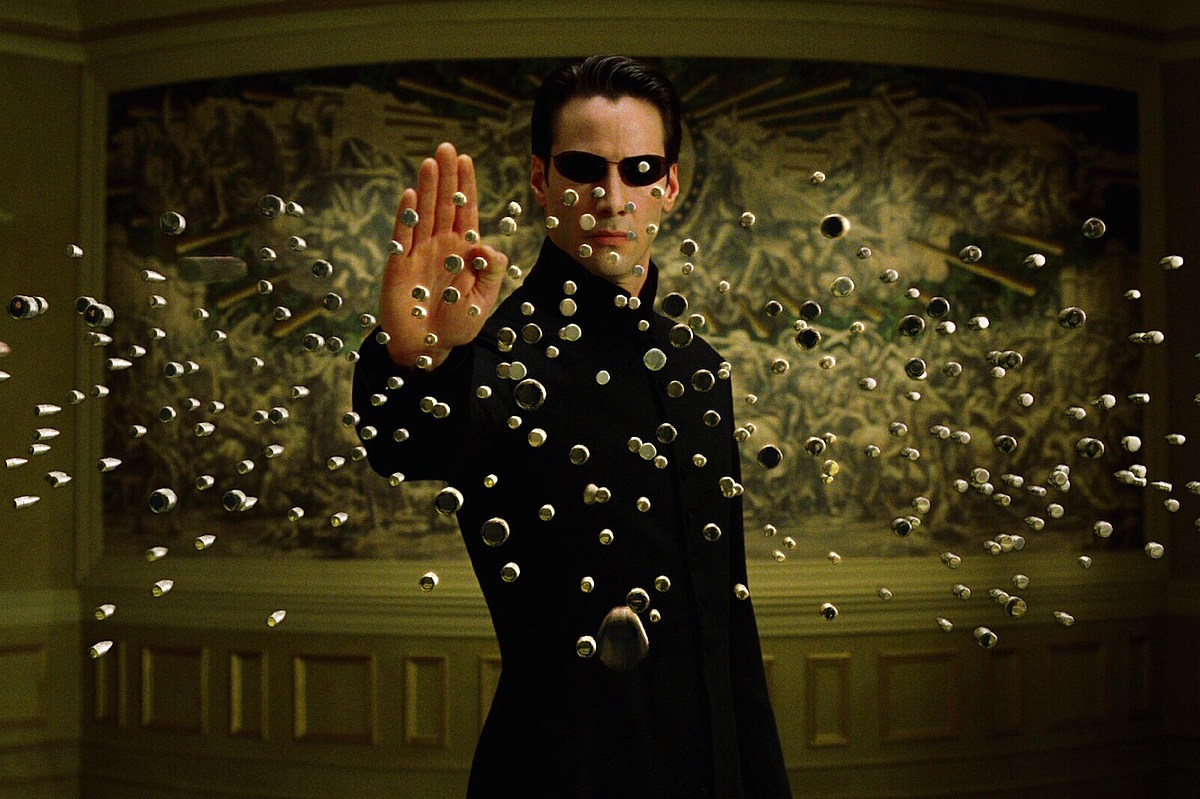 Neo (Keanu Reeves) kan stoppa kulor genom att vifta med handen. Realistiskt? Nej. Coolt? Ja. Foto: Warner Bros. Pictures.