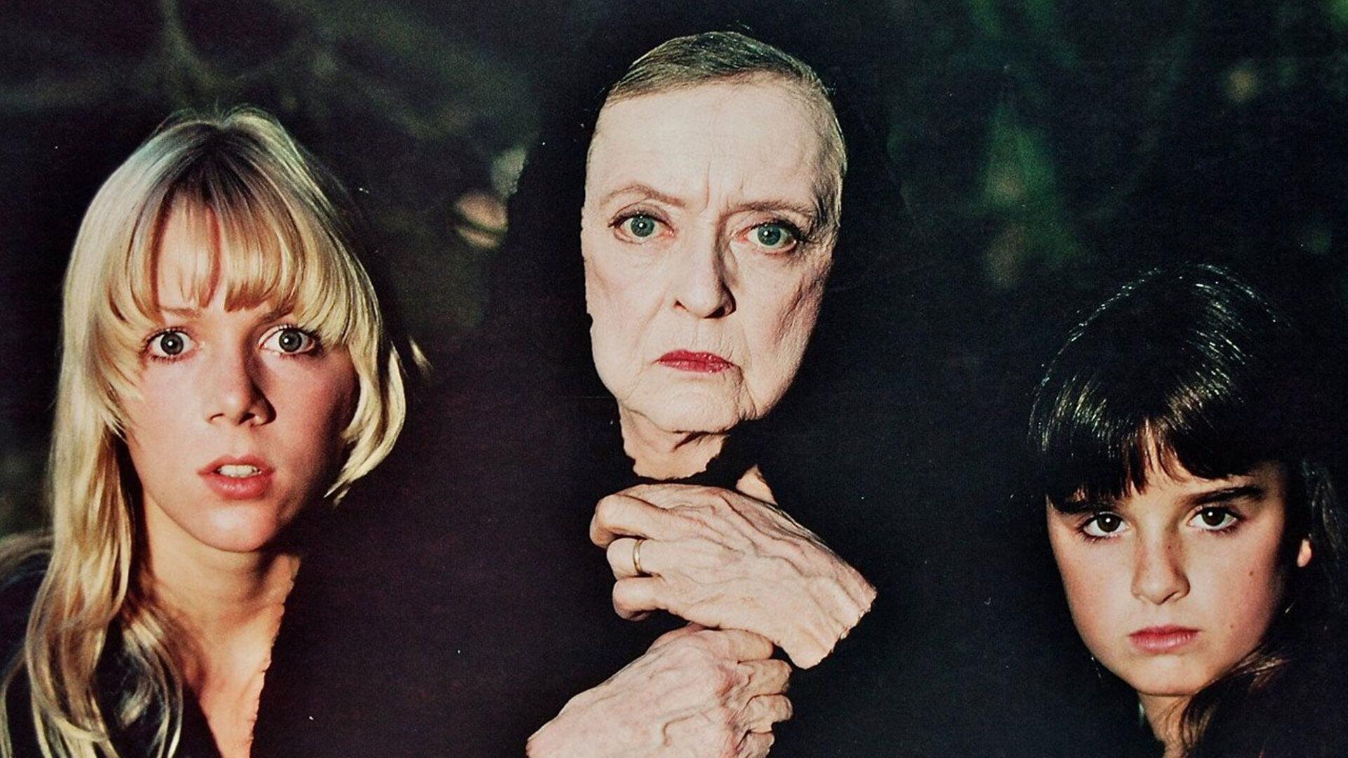 Tre damer beskådar något läskigt i Watcher in the Woods