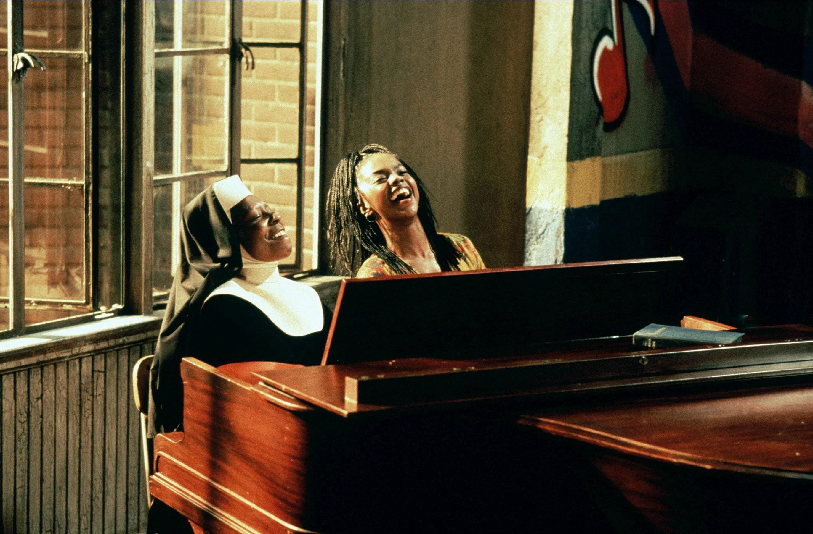 Två damer sjunger bakom ett piano